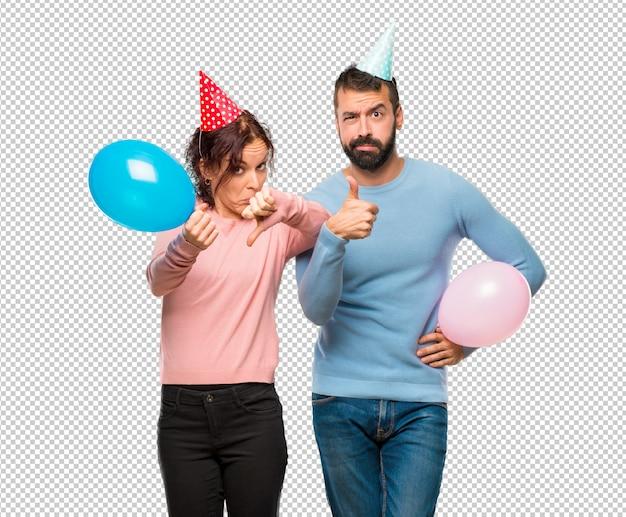 Casal com balões e chapéus de aniversário fazendo bom sinal ruim. indeciso entre sim ou não