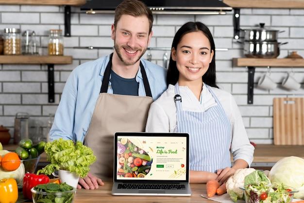 Casal com comida saudável na maquete da cozinha