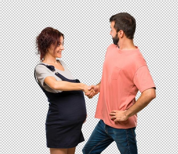 Casal com mulher grávida apertando as mãos para fechar um bom negócio