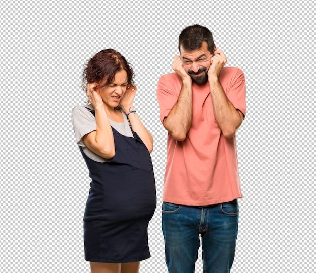 Casal com mulher grávida, cobrindo as orelhas com as mãos. expressão frustrada