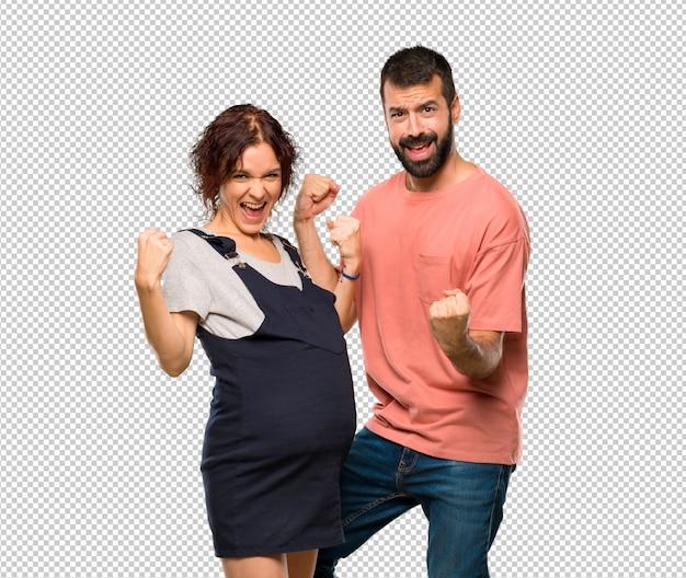 Casal com mulher grávida comemorando uma vitória e feliz por ter ganho um prêmio