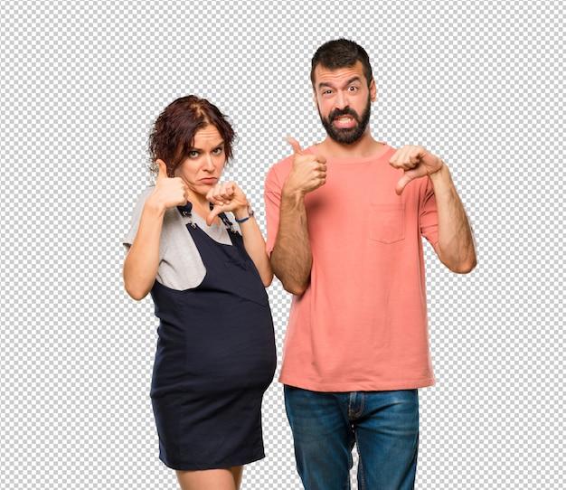 Casal com mulher grávida fazendo bom sinal ruim. indeciso entre sim ou não