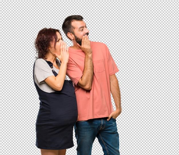 Casal com mulher grávida gritando com a boca aberta e anunciando algo