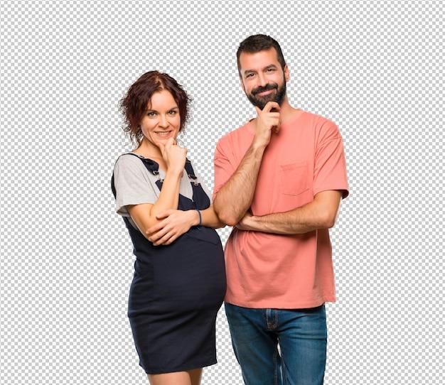 Casal com mulher grávida sorrindo e olhando para a frente com cara confiante
