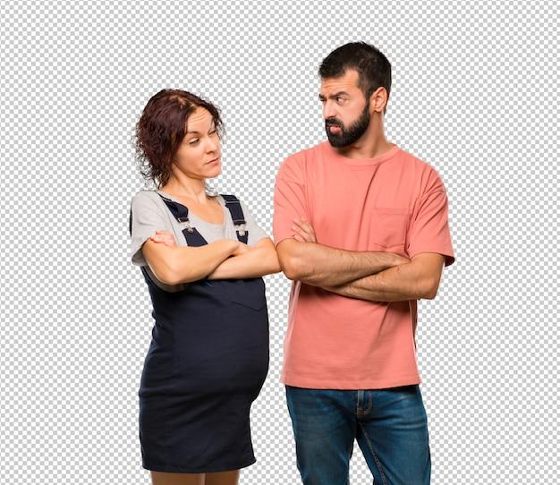 Casal com mulher grávida, tendo dúvidas e com expressão de rosto confuso enquanto morde o lábio