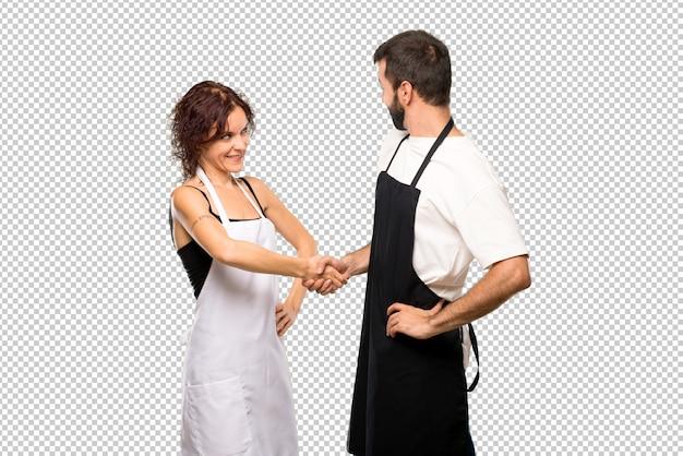 Casal de cozinheiros apertando as mãos para fechar um bom negócio
