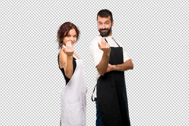 Casal de cozinheiros apresentando e convidando para vir com a mão