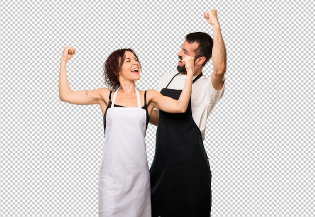 Casal de cozinheiros comemorando uma vitória na posição de vencedor