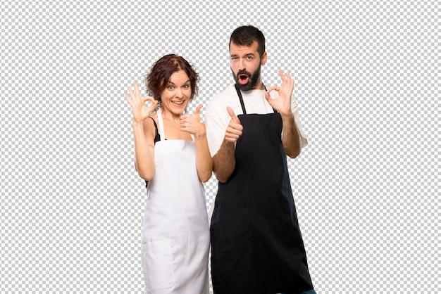 Casal de cozinheiros mostrando sinal de ok e dando um polegar para cima gesto com a outra mão