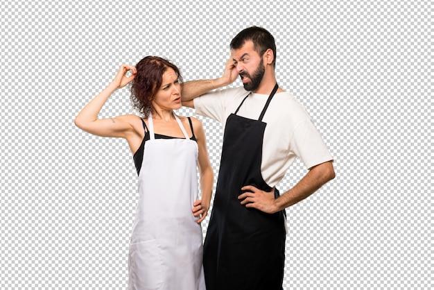 Casal de cozinheiros tendo dúvidas e com confundir o rosto enquanto coçando a cabeça