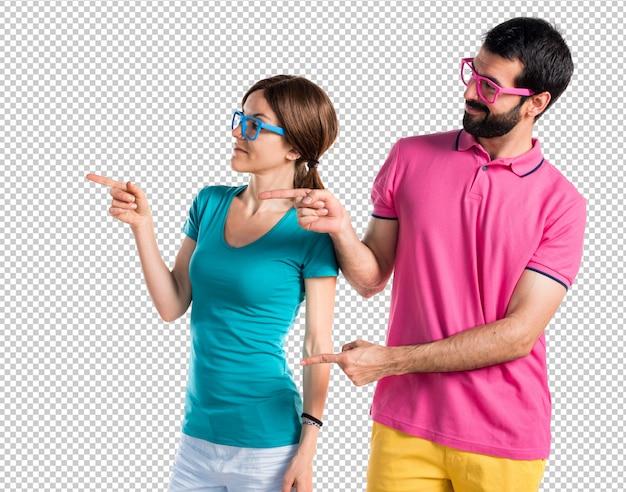 Casal em roupas coloridas, apontando para o lateral