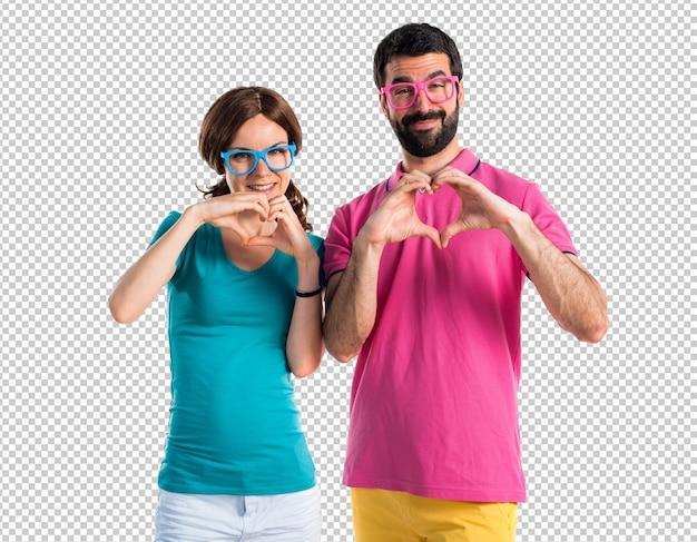 Casal em roupas coloridas, fazendo um coração com as mãos