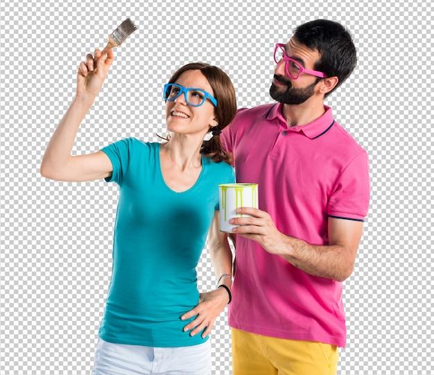 Casal em roupas coloridas, segurando um pote de tinta