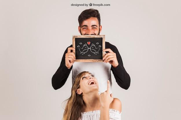 Casal engraçado mostrando ardósia