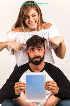 Casal engraçado que apresenta o tablet