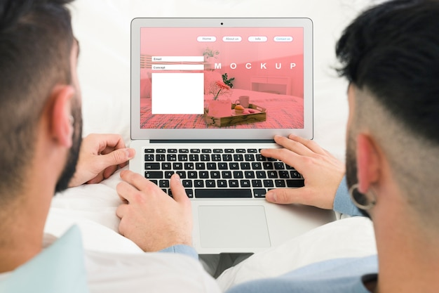 Casal gay e laptop maquete