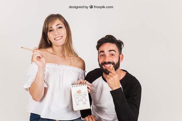 Casal jovem segurando bloco de notas