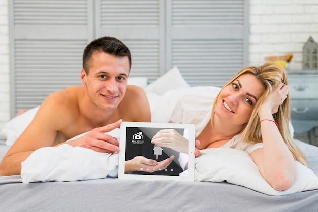 Casal na cama com maquete de tablet para dia dos namorados