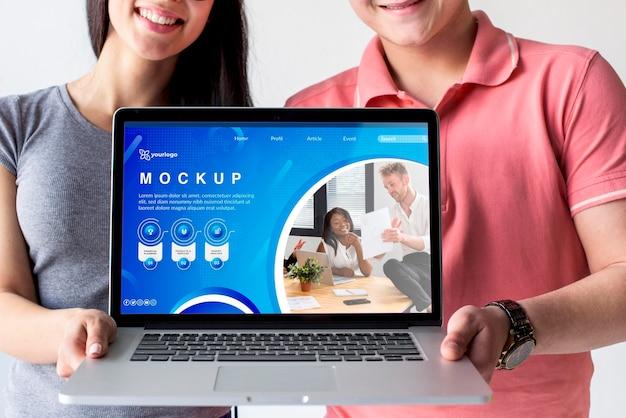 Casal segurando uma maquete de laptop