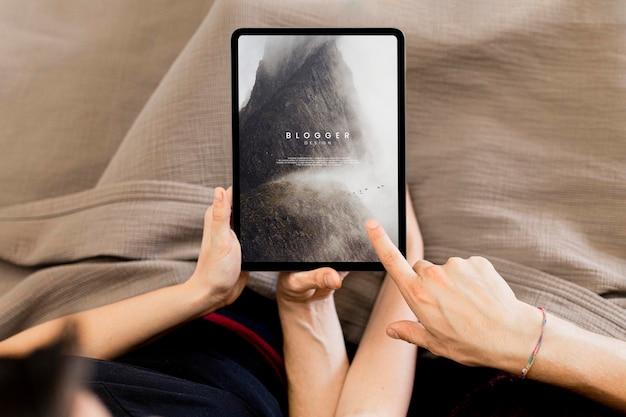Casal usando uma maquete de tela do tablet na cama Psd Premium