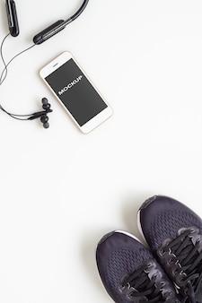 Celular com fone de ouvido bluetooth e tênis no fundo branco