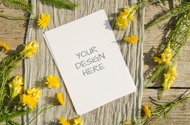 Cena de maquete de artigos de papelaria de verão com flores amarelas em madeira velha