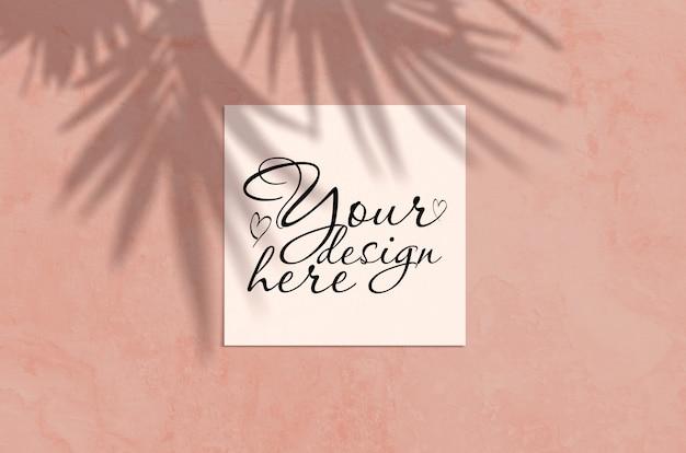 Cena moderna do modelo dos artigos de papelaria da luz solar do verão. flat lay top view cartão em branco com folha de palmeira e sobreposição de sombra de ramos
