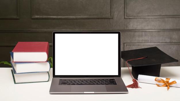 Chapéu de formatura e livros com maquete de laptop