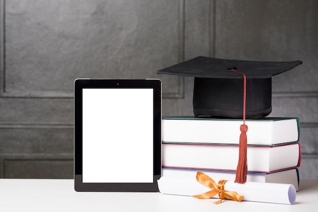 Chapéu de formatura e livros com maquete do tablet