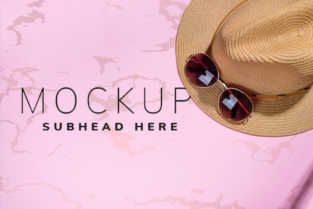 Chapéu e óculos de sol em papel rosa