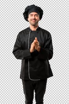 Chef homem de uniforme preto aplaudindo após apresentação em uma conferência