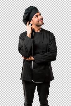 Chef homem em uniforme preto em pé e pensando uma idéia enquanto coçando a cabeça