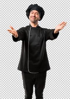 Chef man em uniforme preto apresentando e convidando para vir com a mão. feliz que você veio