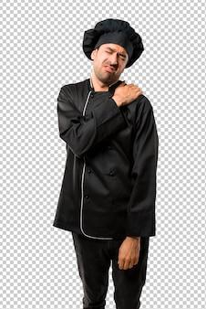 Chef man em uniforme preto, sofrendo de dor no ombro por ter feito um esforço