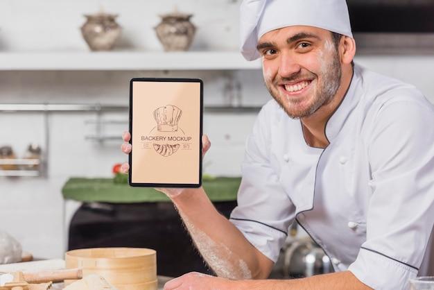 Chef sorridente na maquete da cozinha
