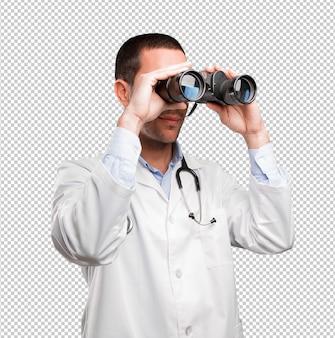 Chocado jovem médico usando um binóculo