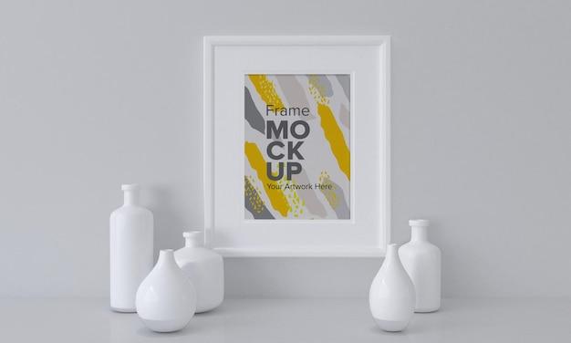 Close de uma maquete de moldura branca ao lado de vasos em um fundo de parede cinza