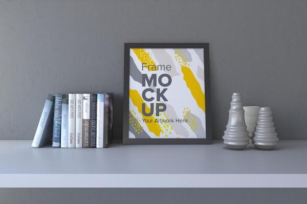 Close de uma moldura preta com vasos e livros em uma maquete de moldura de fundo de parede cinza