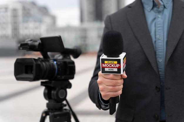 Close no repórter segurando a maquete do microfone