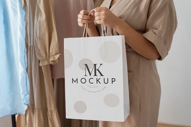 Close-up com as mãos segurando uma sacola de compras