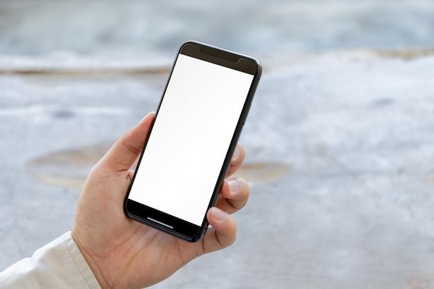 Close up da mão do homem novo usando smartphone móvel com fundo desfocado