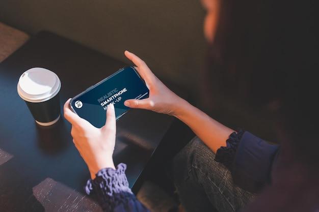 Close-up da mulher usando smartphone no café.