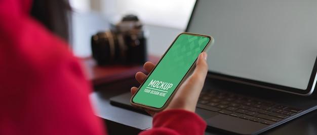 Close-up de mãos femininas segurando uma maquete de smartphone