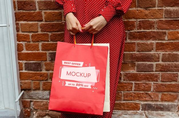 Close-up de mãos segurando sacolas de compras
