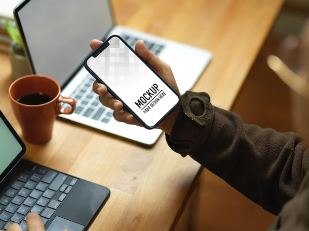 Close-up de uma mão masculina segurando uma maquete de smartphone