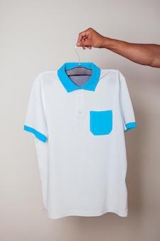 Close-up em jovem segurando uma camiseta de maquete