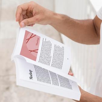 Close-up homem na rua lendo livro
