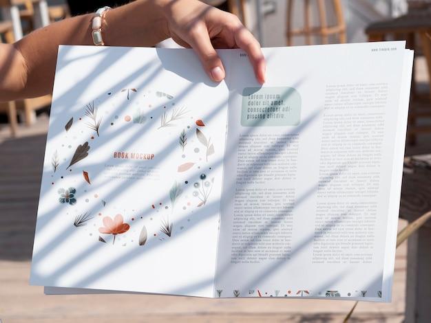 Close-up mão segurando uma revista de natureza simulada