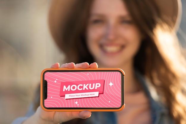 Close-up mulher embaçada segurando um smartphone
