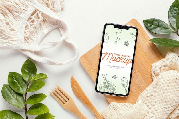 Close-up na maquete de smartphone perto de objetos sustentáveis